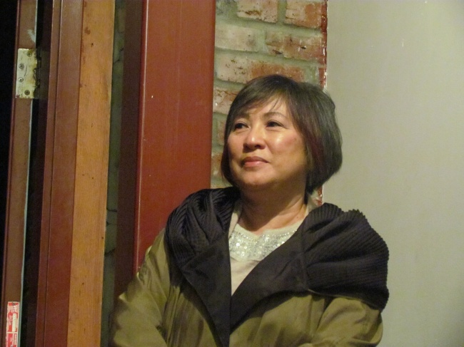Jo-anne Lee stands and watches poetry at intergeneration event at Solstice Cafe.