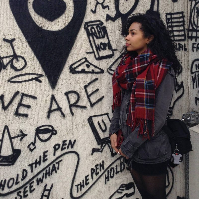 Emery stands by a wall covered in art, in Harajuku Japan.
